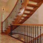 Curved maple staircase with open risers & metal balusters